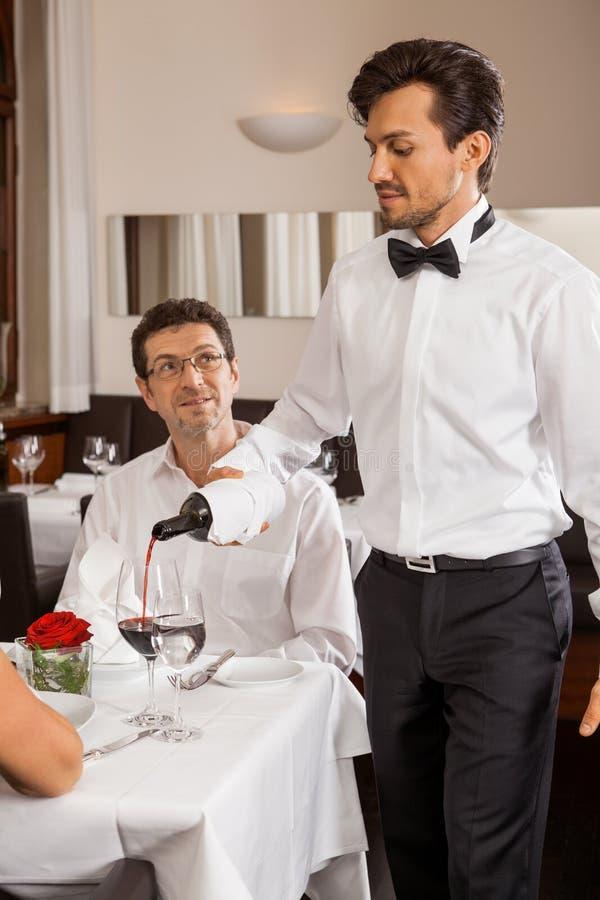 Kellner, der ein Paar in einem Restaurant dient stockfotografie
