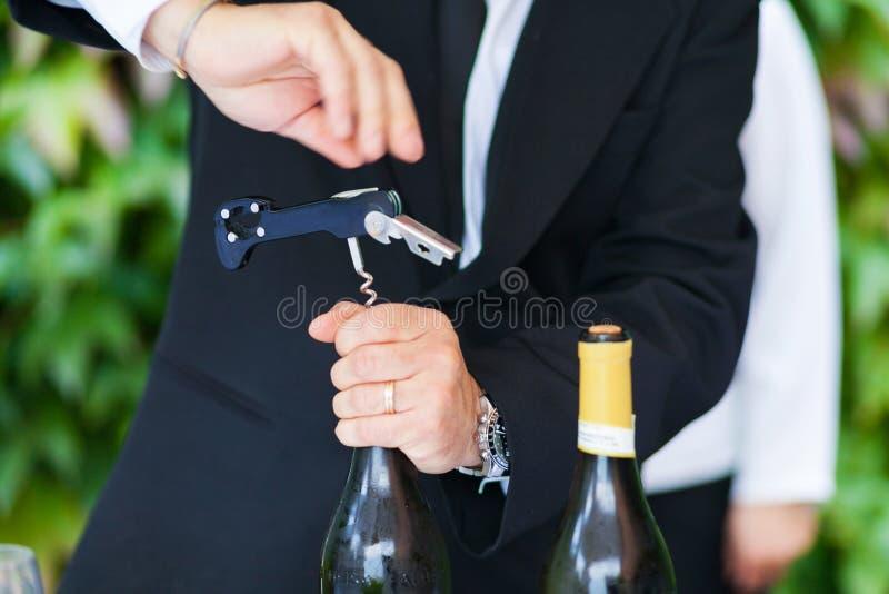 Kellner, der eine Flasche weißen Wein öffnet lizenzfreies stockbild