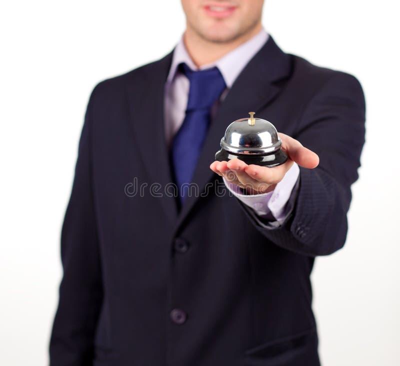 Kellner, der eine Hotelglocke anhält lizenzfreie stockfotos