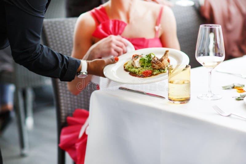 Kellner, der eine Platte mit Salatteller auf einer Hochzeit trägt. stockbild