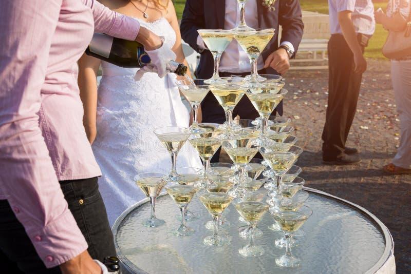 Kellner, der eine Pyramide von Gläsern mit Champagner Garten am im Freien in der Hochzeitszeremonie füllt lizenzfreies stockfoto