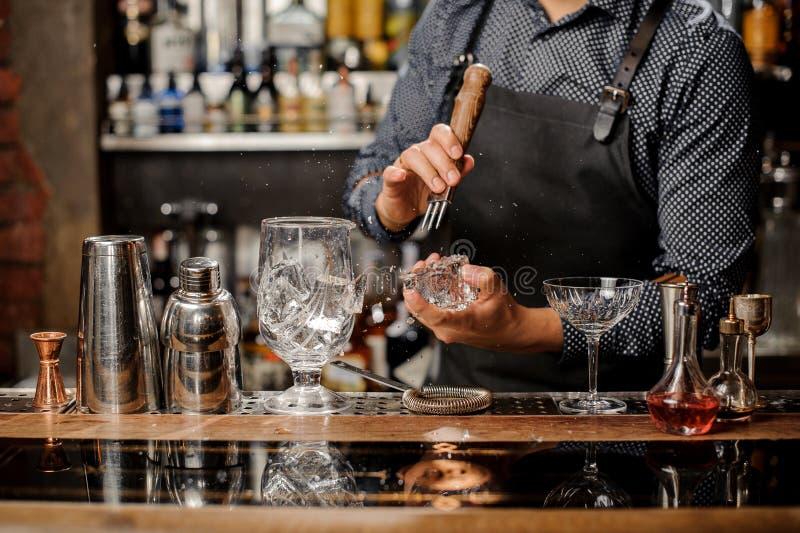 Kellner, der einen großen Eiswürfel für die Herstellung eines Cocktails zerquetscht stockfoto