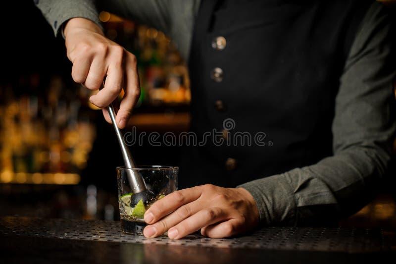 Kellner, der einen Rohrzucker mit Kalk im Glas mischt stockbild