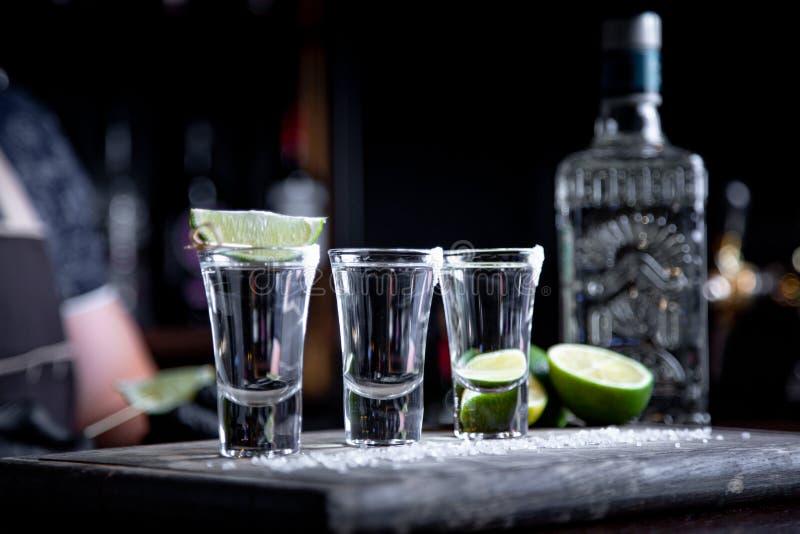 Kellner, der harten Geist in kleine Gläser wie alkoholische Schüsse von Tequila oder von alkoholischem Getränk gießt lizenzfreies stockfoto