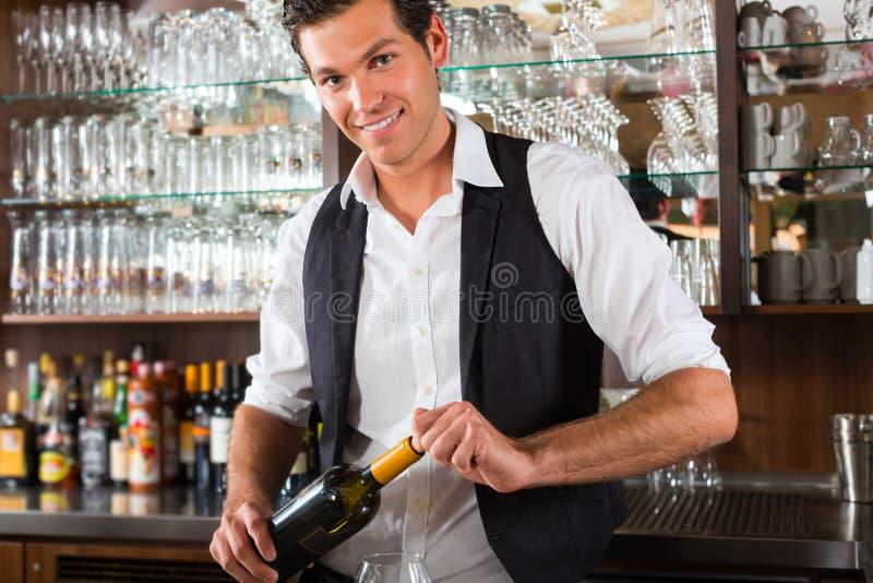 Kellner, der hinter Bar mit Wein steht stockbild