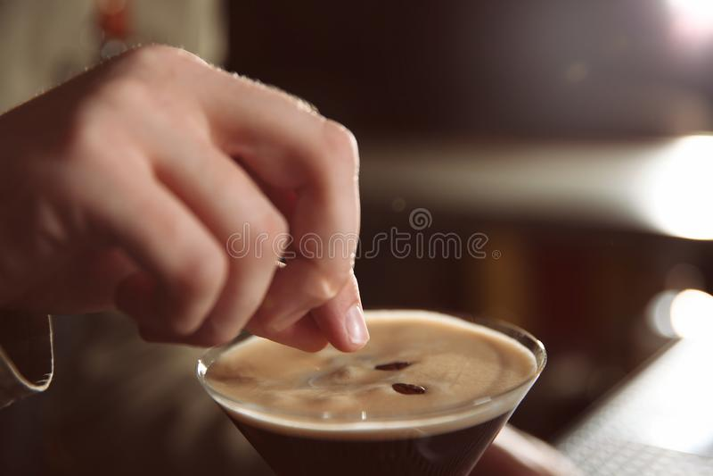 Kellner, der Kaffeebohne Martini-Espressococktail hinzufügt lizenzfreies stockbild
