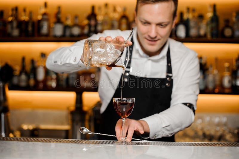Kellner an der Kneipe gießt kalten Whisky im Becher stockfotografie