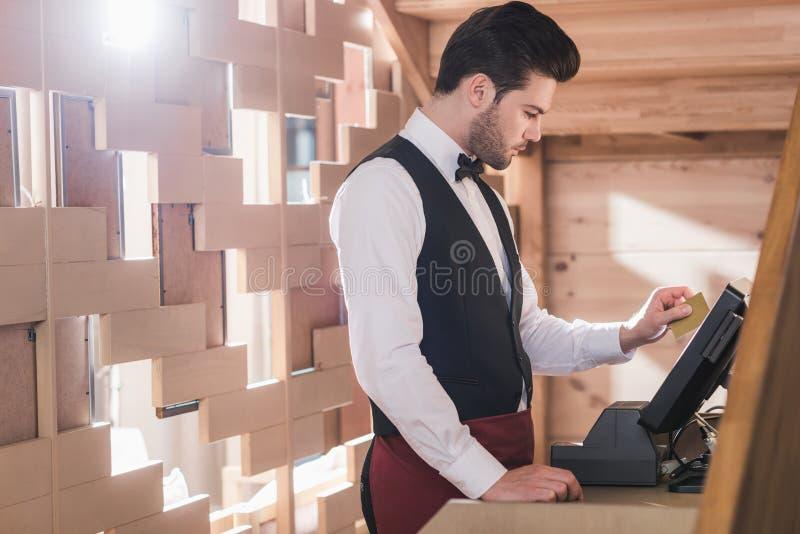 Kellner, der an der Registrierkasse steht stockfoto
