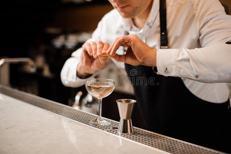 Kellner, der Saft der Zitronenschale in ein Cocktailglas besprüht lizenzfreies stockbild