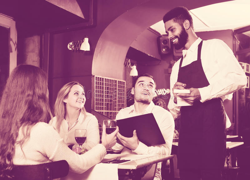 Kellner, der um Erwachsenen am Cafétisch sich kümmert lizenzfreie stockfotos