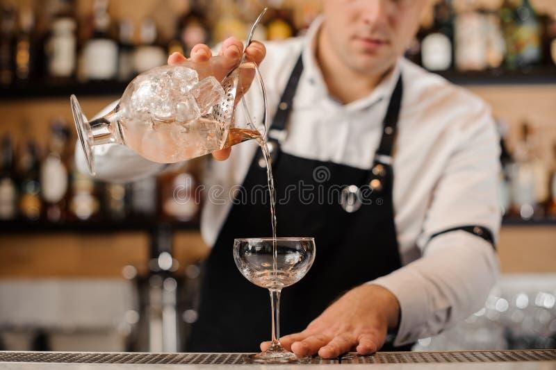 Kellner, der Wodka in ein Cocktailglas hinzufügt lizenzfreie stockbilder