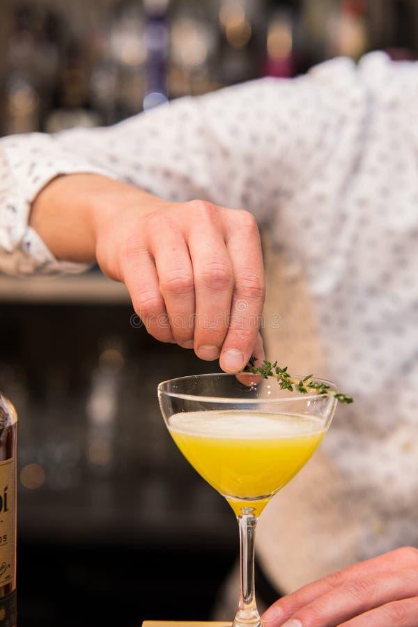Kellner, der Zitronenschale setzt, um coctail vorzubereiten lizenzfreies stockfoto