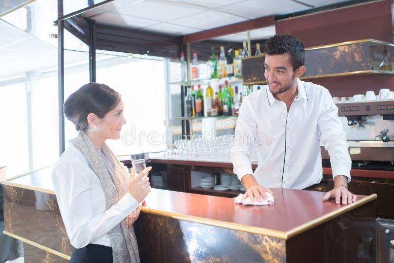 Kellner, der zum hübschen Kunden in der Stange plaudert lizenzfreies stockfoto