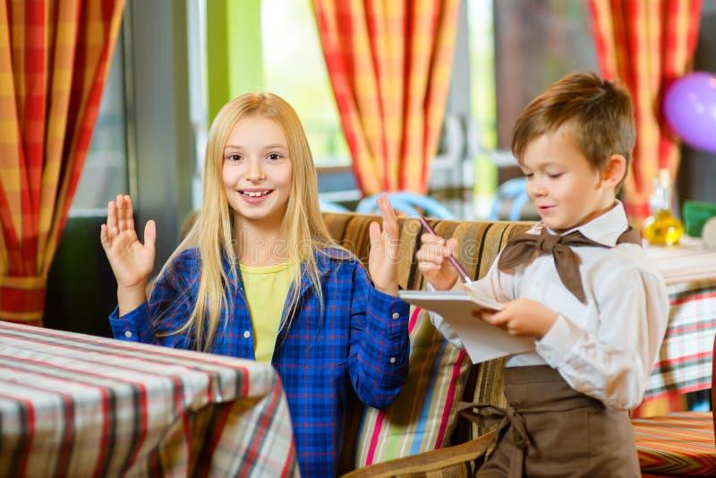 Kellner des kleinen Jungen nimmt die Bestellung in einem Café an oder stockfotografie