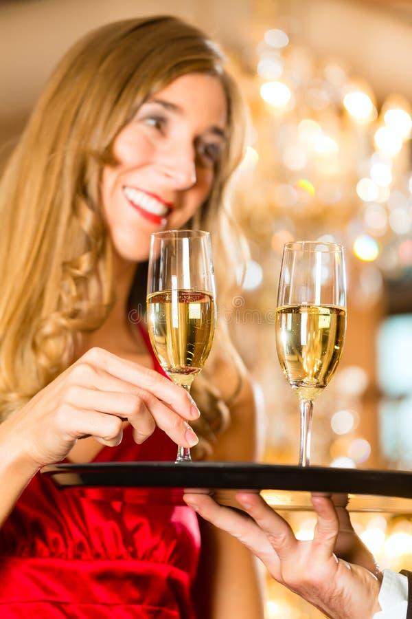 Kellner dient Champagnergläser auf Behälter im Restaurant stockfotos