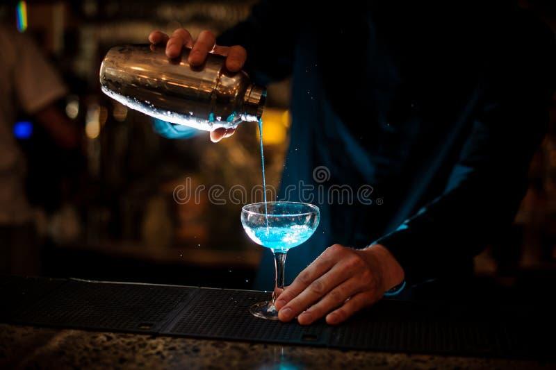Kellner gießt aus einem Schüttel-Apparat in ein Glas der Alkoholcocktail Blau-Lagune stockbilder
