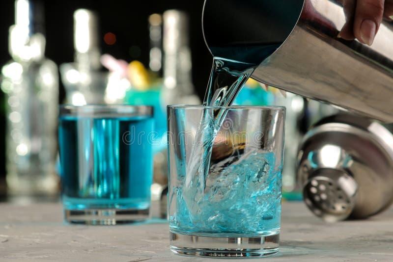 Kellner gießt ein blaues Lagunencocktail von einem Schüttel-Apparat in ein Glas an der Bar Cocktailvorbereitung lizenzfreie stockfotografie
