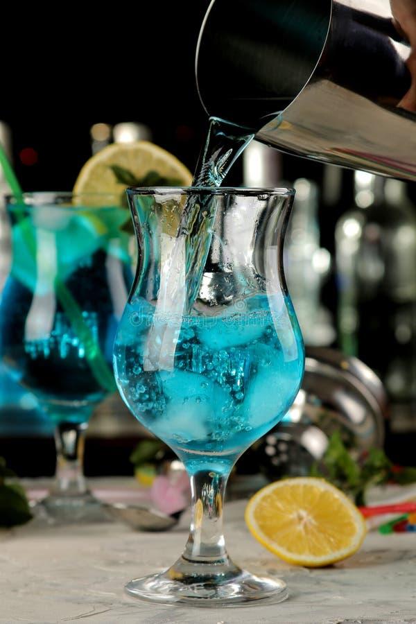 Kellner gießt ein blaues Lagunencocktail von einem Schüttel-Apparat in ein Glas an der Bar Cocktailvorbereitung lizenzfreies stockbild