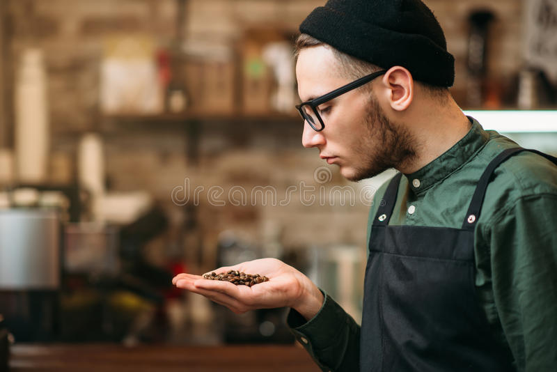 Kellner hält in einem Palmenkorn des Kaffees stockbild