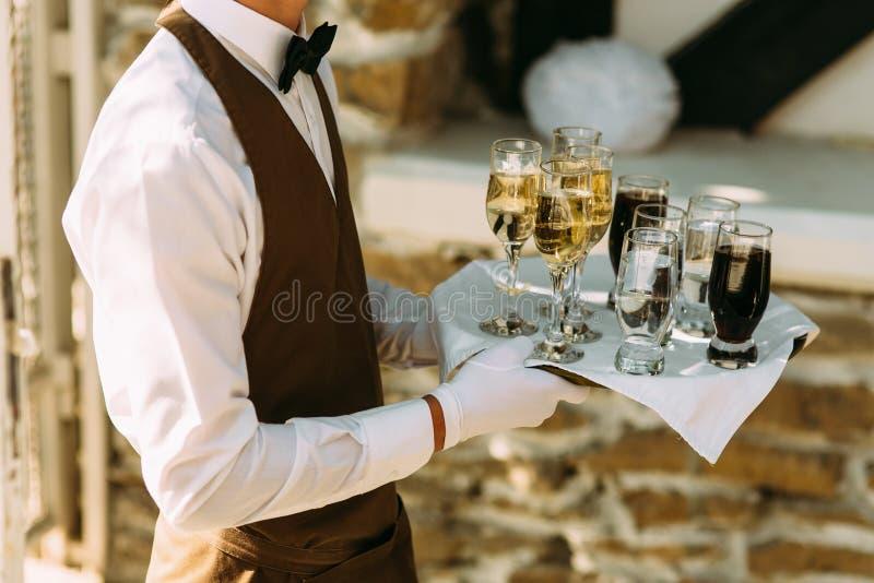 Kellner hält einen Server mit den Alkoholgetränken stockfoto