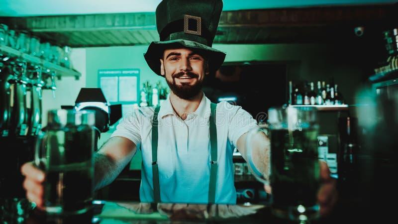 Kellner-Holds Glasses With-Bier St Patrick ` s Tag lizenzfreie stockfotos