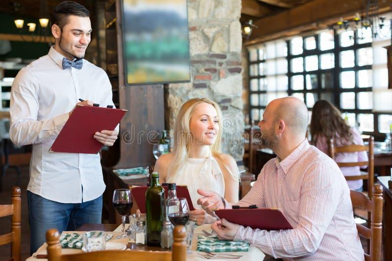 Kellner mit Restaurantgästen bei Tisch lizenzfreie stockfotos