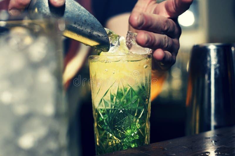Kellner setzt Eis in ein Cocktail ein lizenzfreie stockbilder