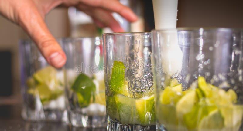 Kellner zerquetscht grüne Zitronen mit einer Pille, um caipirihnas zu machen lizenzfreie stockbilder