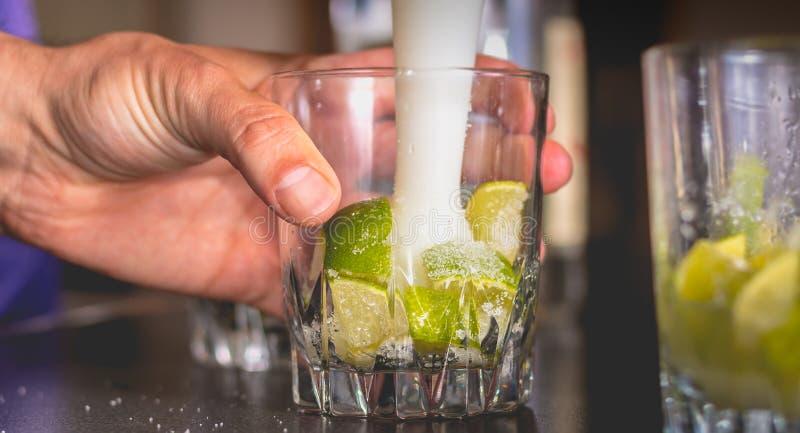 Kellner zerquetscht grüne Zitronen mit einer Pille, um caipirihnas zu machen lizenzfreie stockfotografie