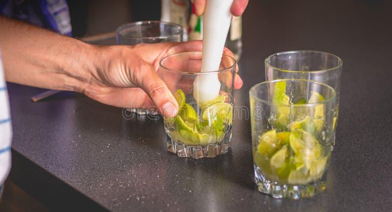 Kellner zerquetscht grüne Zitronen mit einer Pille, um caipirihnas zu machen stockfotografie