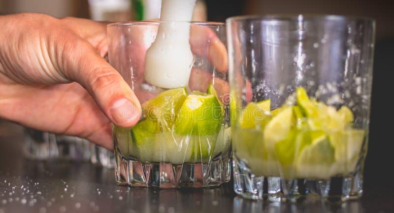 Kellner zerquetscht grüne Zitronen mit einer Pille, um caipirihnas zu machen stockbild