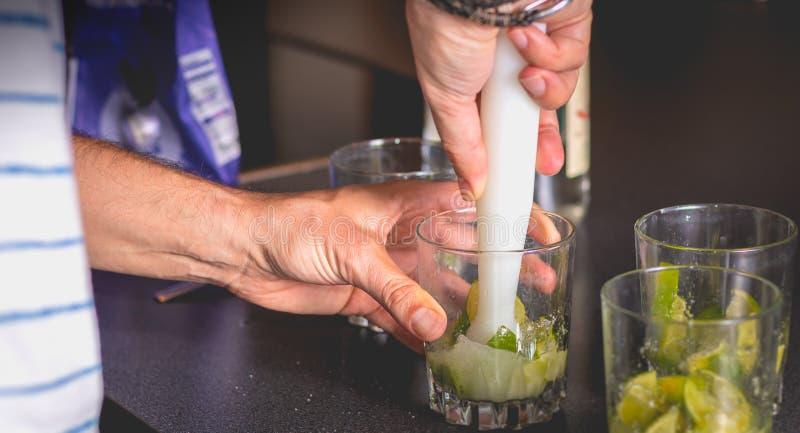 Kellner zerquetscht grüne Zitronen mit einer Pille, um caipirihnas zu machen stockfoto