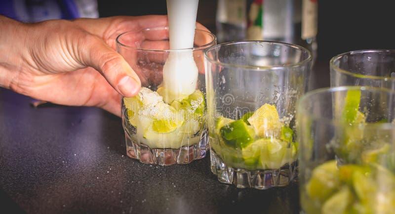 Kellner zerquetscht grüne Zitronen mit einer Pille, um caipirihnas zu machen stockbilder
