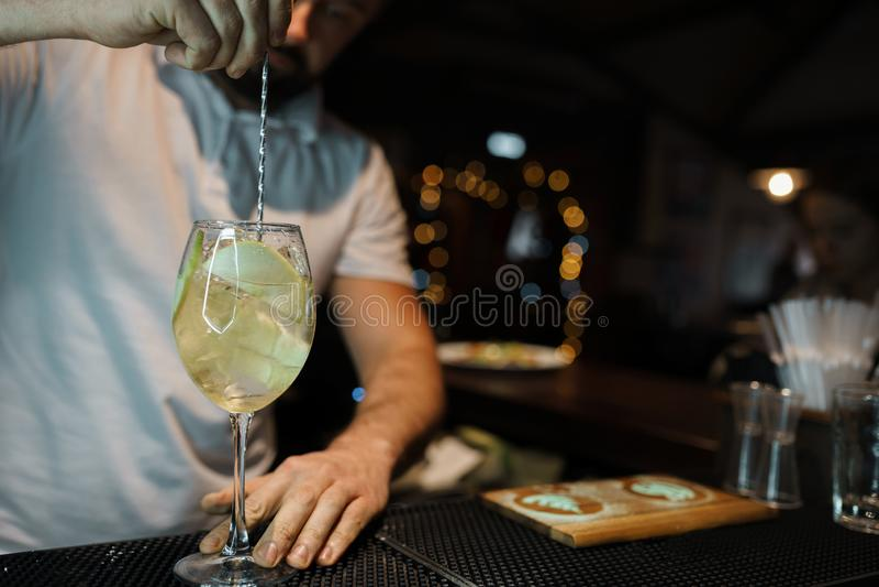 Kellnerfachmann im weißen T-Shirt, das hinter dem Tresen in einer Bar steht und macht ein köstliches alkoholisches Cocktail mit A lizenzfreie stockfotos