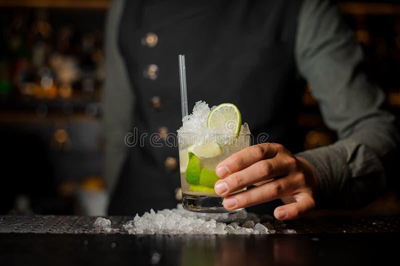 Kellnerhand, die ein Glas mit einem frischen mojito hält stockfotografie