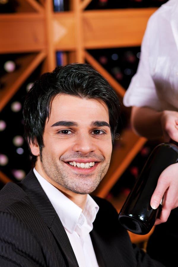 Kellnerin in der Gaststätte, die Rotwein anbietet stockbilder