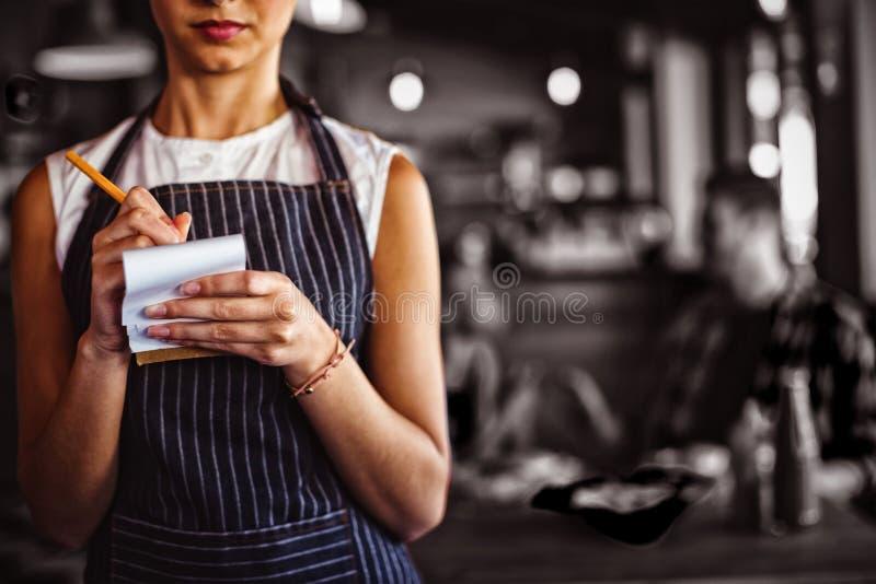 Kellnerin, die Bestellung am Restaurant entgegennimmt lizenzfreie stockbilder