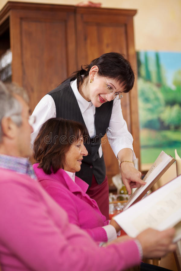 Kellnerin, die Gast erklärt lizenzfreie stockfotos