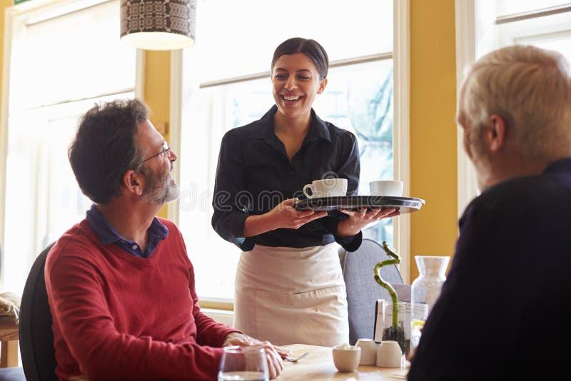 Kellnerin, die Kaffee zu einem männlichen Paar an einem Restaurant holt stockfotografie