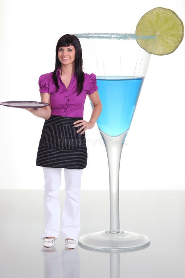 Kellnerin, die nahe bei Cocktail steht stockbild