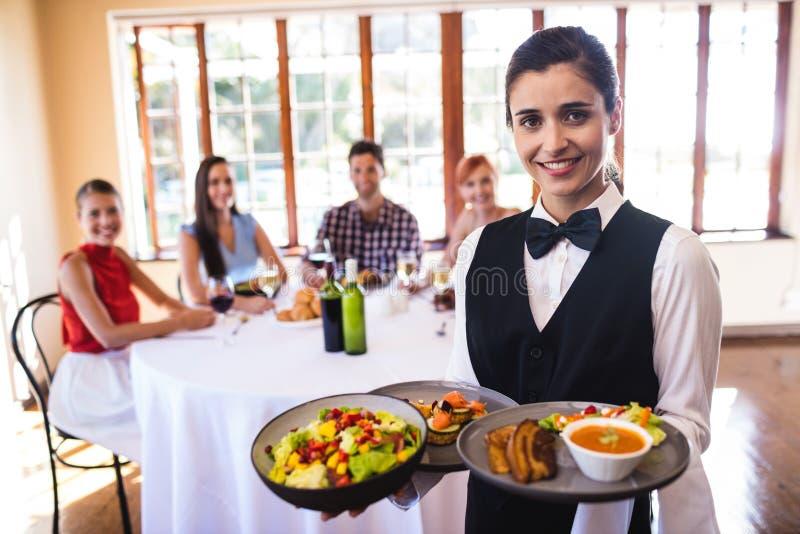 Kellnerin, die Nahrung auf Platte im Restaurant hält stockfotos