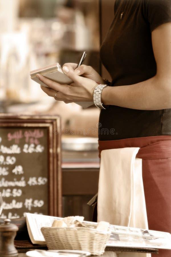 Kellnerin, die Ordnung nimmt stockfotografie