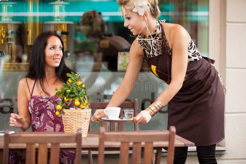 Kellnerin mit einem Behälter in einer Kaffeestube stockfotos