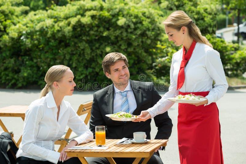 Kellnerin-Serving Food To-Wirtschaftler lizenzfreie stockbilder