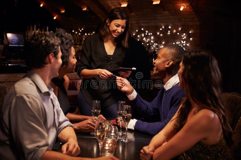 Kellnerin-Takes Payment For-Restaurant Bill On Digital Tablet lizenzfreies stockbild