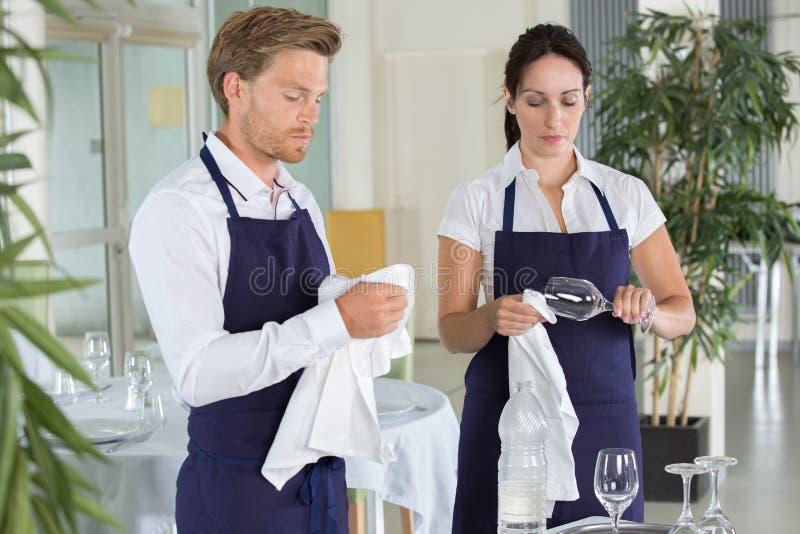 Kellnerin- und Kellnerreinigungsgläser im Restaurant lizenzfreie stockfotos