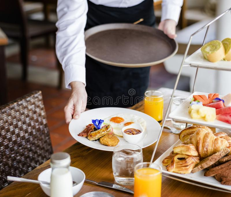 Kellnerinumhüllungsfrühstück an einem Restaurant stockfotos