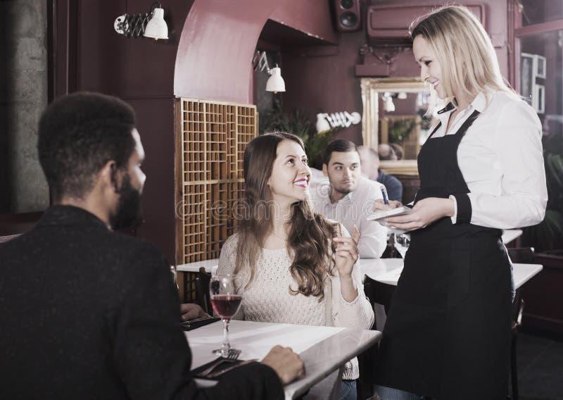 Kellnerinumhüllungsmahlzeit für junge Paare bei Tisch stockfotos