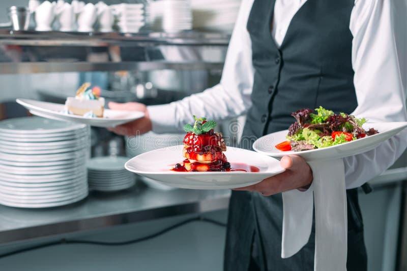 Kellnerumh?llung in der Bewegung im Dienst im Restaurant Der Kellner tr?gt Teller lizenzfreies stockfoto