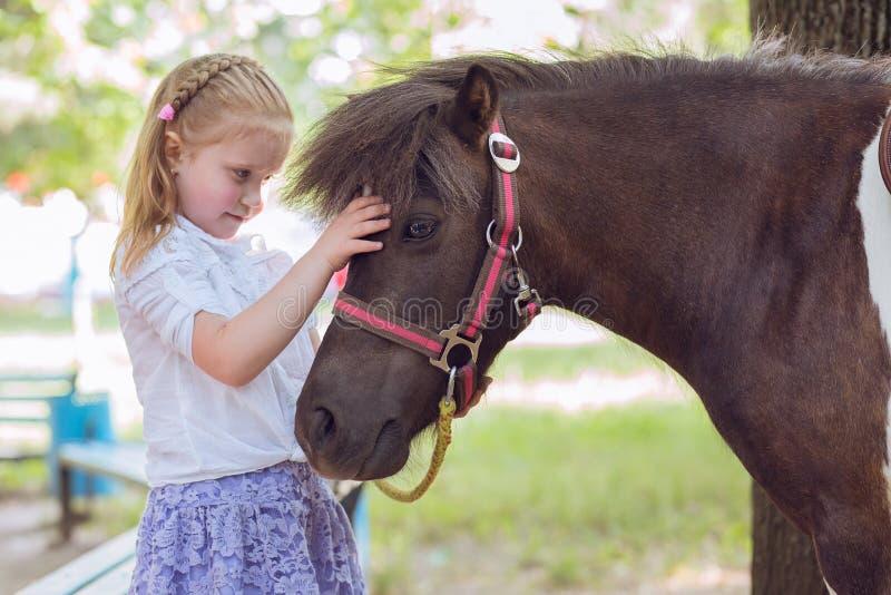 Keln för flicka för liten unge parkerar den hållande hennes gräsplan för yttersidan för ponnyhästen utomhus bakgrund royaltyfria bilder